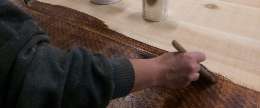Application à la main d'une teinture écologique sur bois brut par un ébéniste
