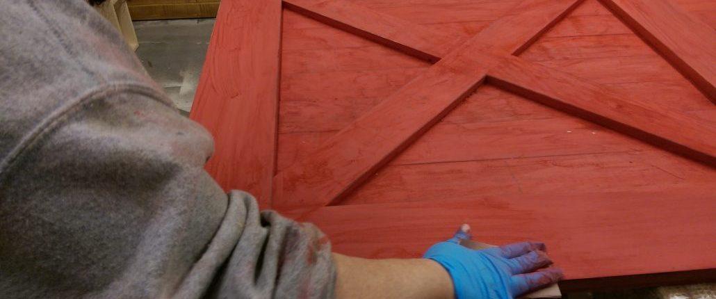 sablage d'un porte de style porte de grange avec une finition à la peinture de lait rouge